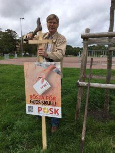 """En man som står i en vägren och sätter upp en valaffisch i gräset genom att slå ned pinnen med baksidan av en yxa. Affischen sitter på ett stort kors och på affischen står det """"Kyrkoval 2017, Rösta för Guds skull! POSK"""""""