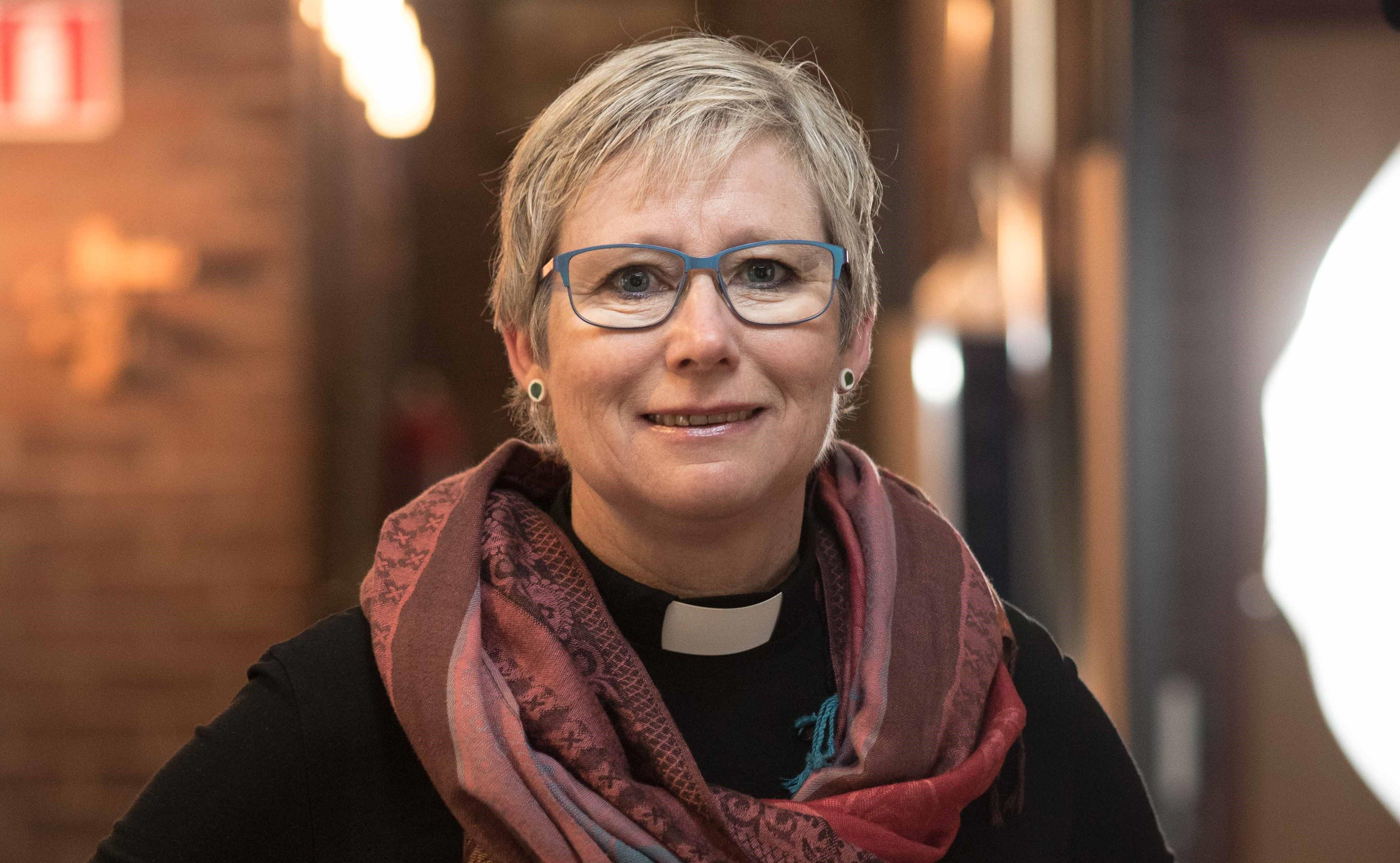 Susanne Rappmann, kort ljust hår och glasögon. Prästskjorta och en sjal i rosa nyanser om halsen