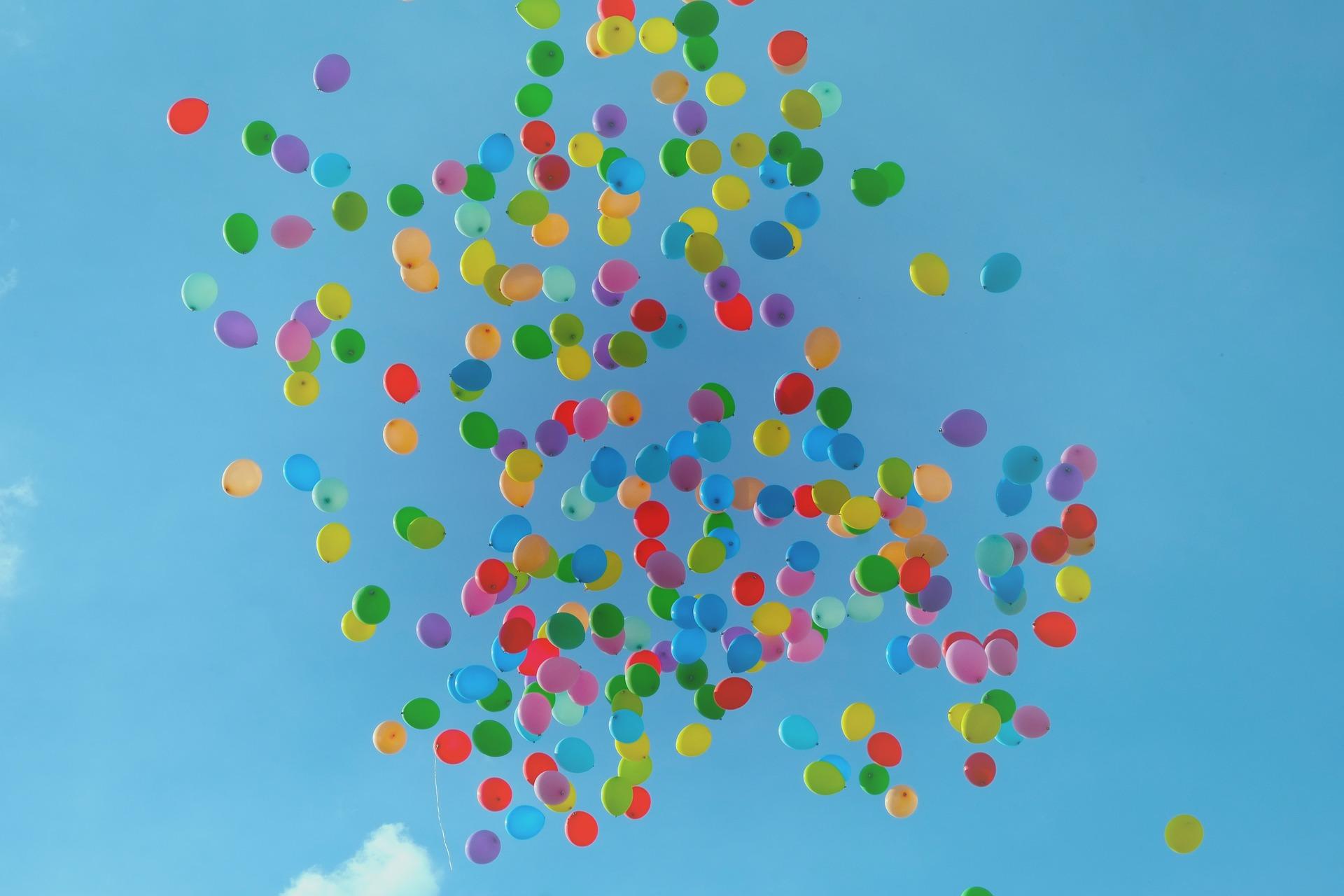 Massor med ballonger som svävar iväg mot en blå himmel