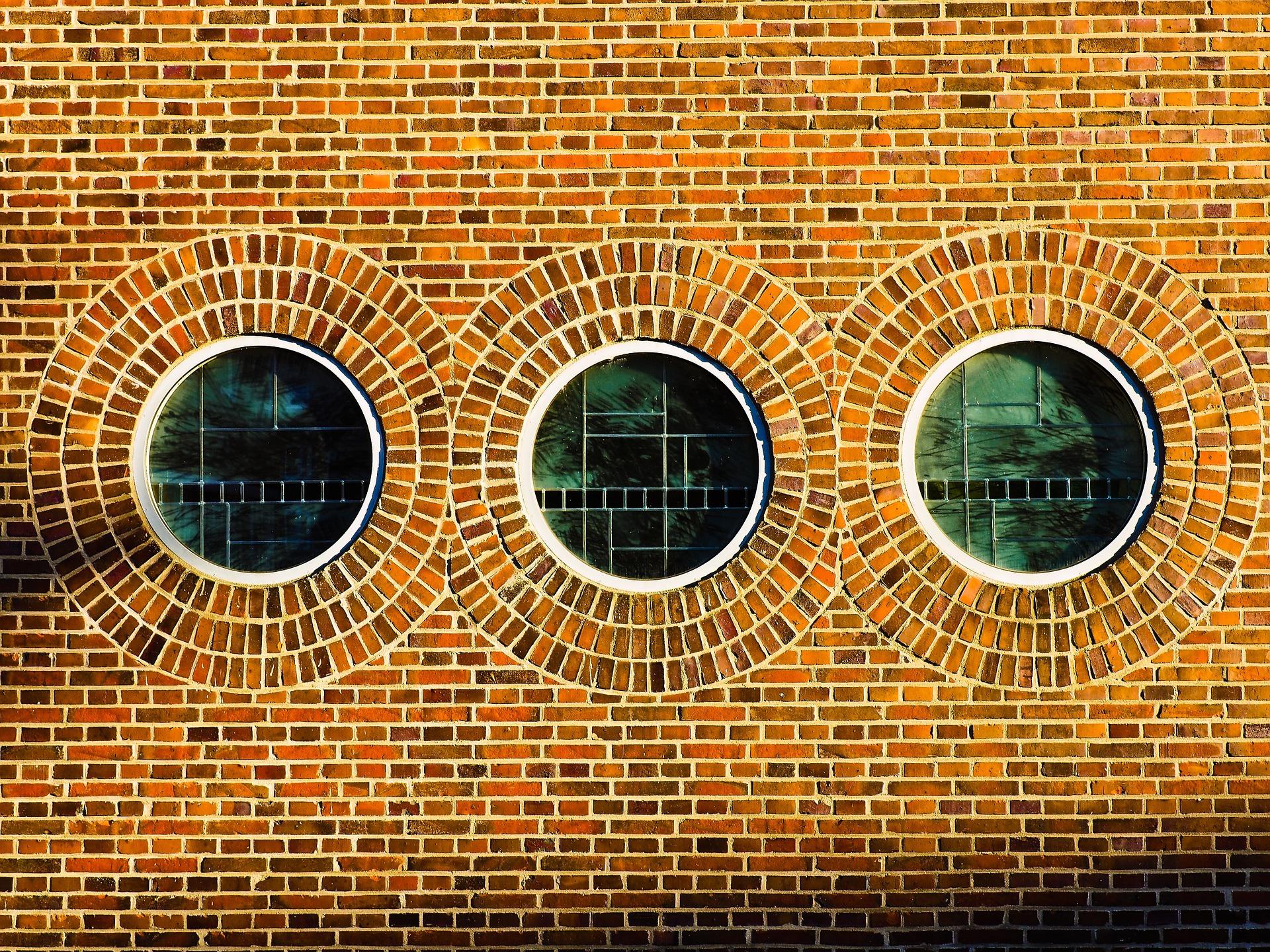 En tegelvägg med tre runda fönster