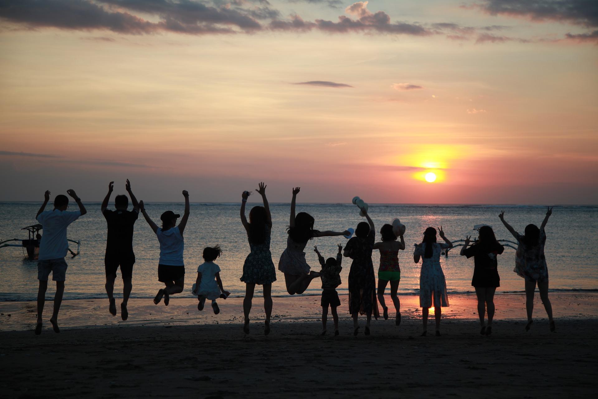 Ett antal hoppande, glada barn på en strand i solnedgång.