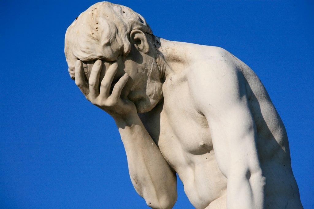 En staty i marmor där figuren håller ansiktet gömt i sin handflata