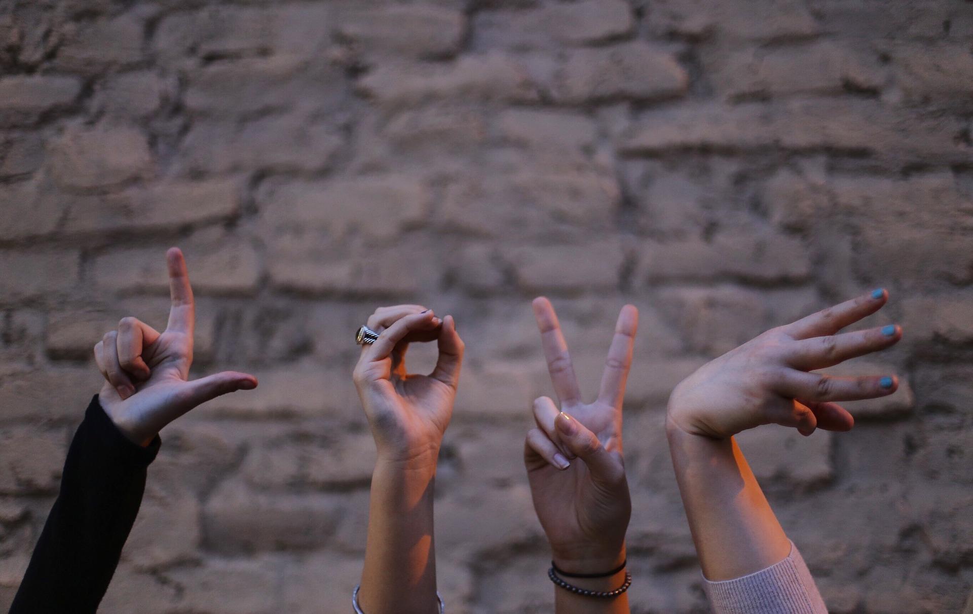 Fyra händer mot en suddig tegelvägg i bakgrunden. Händerna formar ordet LOVE, kärlek på engelska