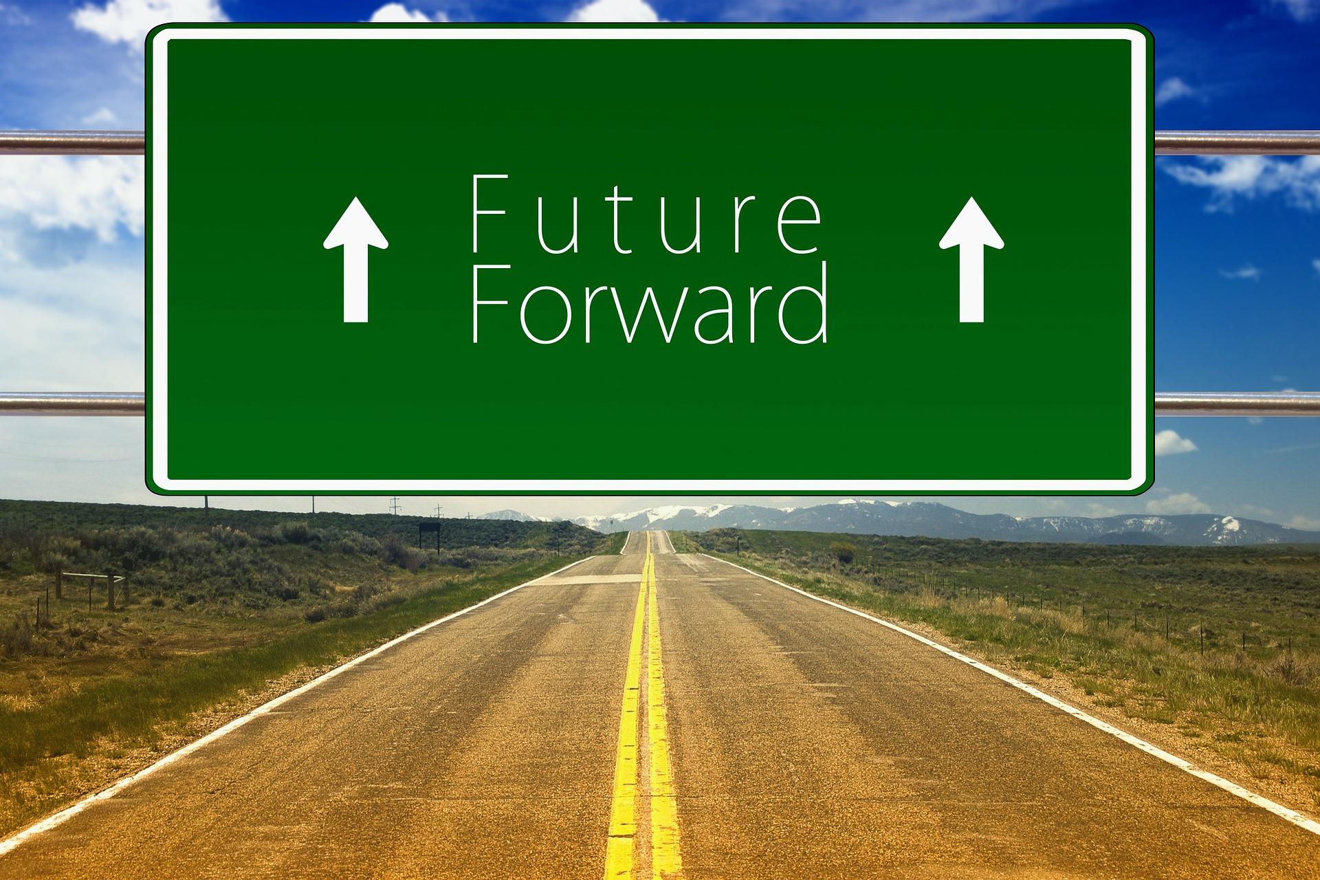 """Lång rak väg genom ett öde landskap med en stor skylt över med texten """"Future Forward"""" och två pilar som pekar uppåt/framåt"""