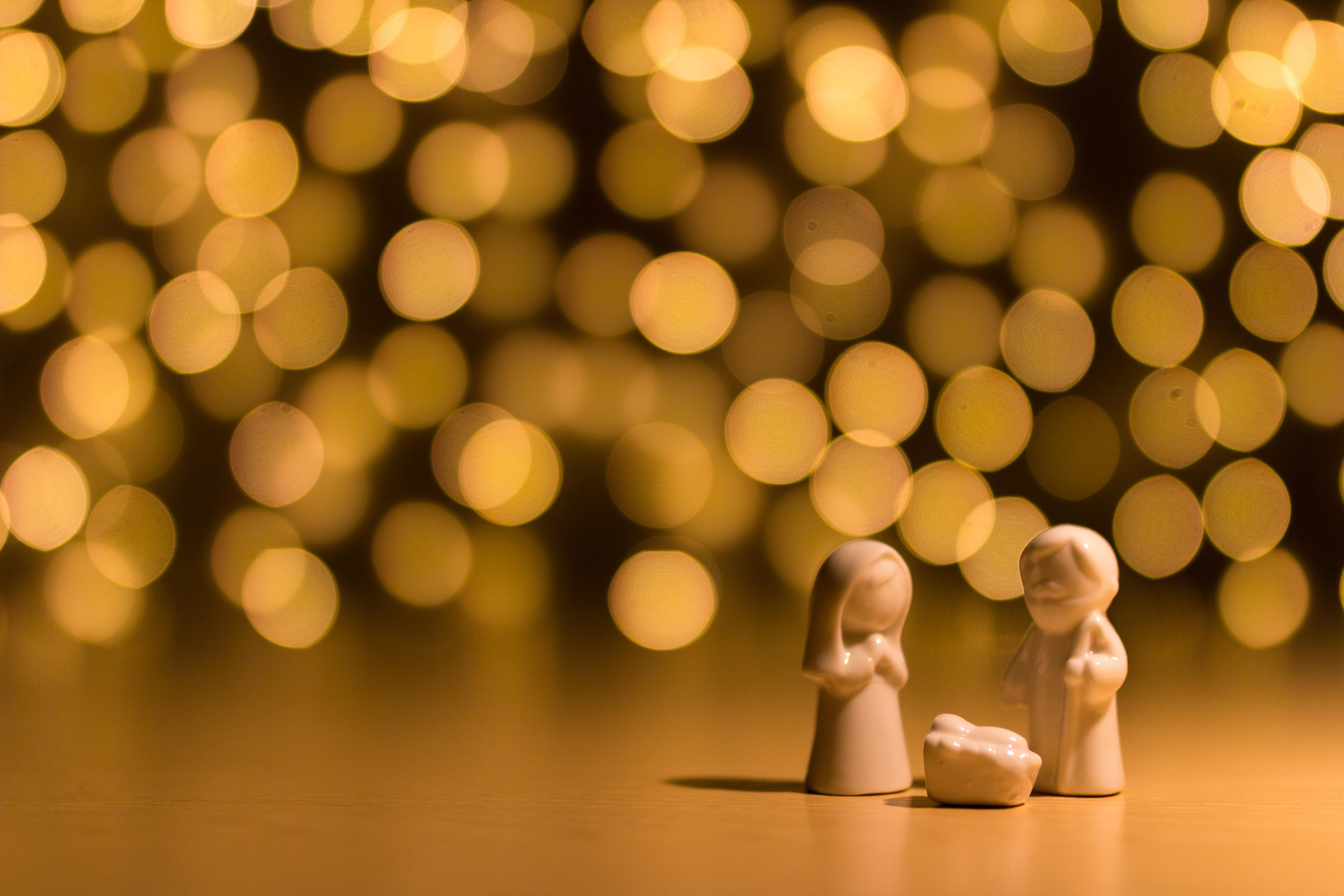 Julkrubbefigurer, Josef, Maria och Jesusbarnet i krubban, framför en massa lampor ur fokus i bakgrunden.