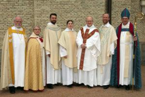 Två biskopar på var sin sida om fem präster, alla högtidsklädda