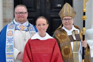 Två präster och en biskop framför en kyrkport