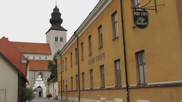 Ett gult hus med texten Visby stift på, med Visby domkyrka i bakgrunden