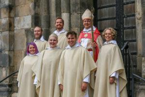 En biskop och sex präster står på en trappen framför en kyrkport