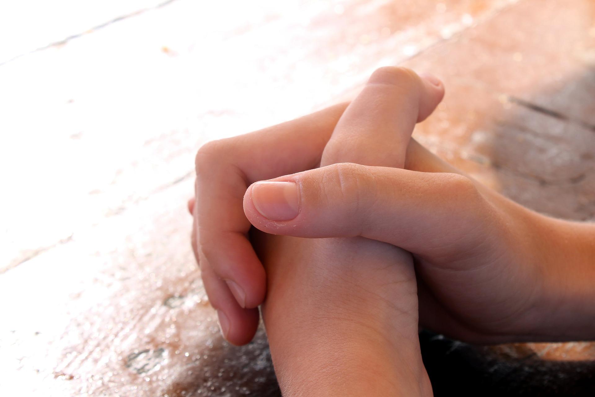 Bild på knäppta händer som ligger mot ett belyst bord