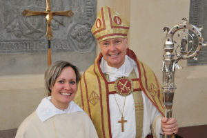 En biskop och en präst står leende framför ett altare i bakgrunden