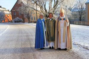 En biskop och två präster står högtidsklädda i ett vintrigt stadslandskap