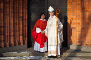 En präst och en biskop framför en kyrkport