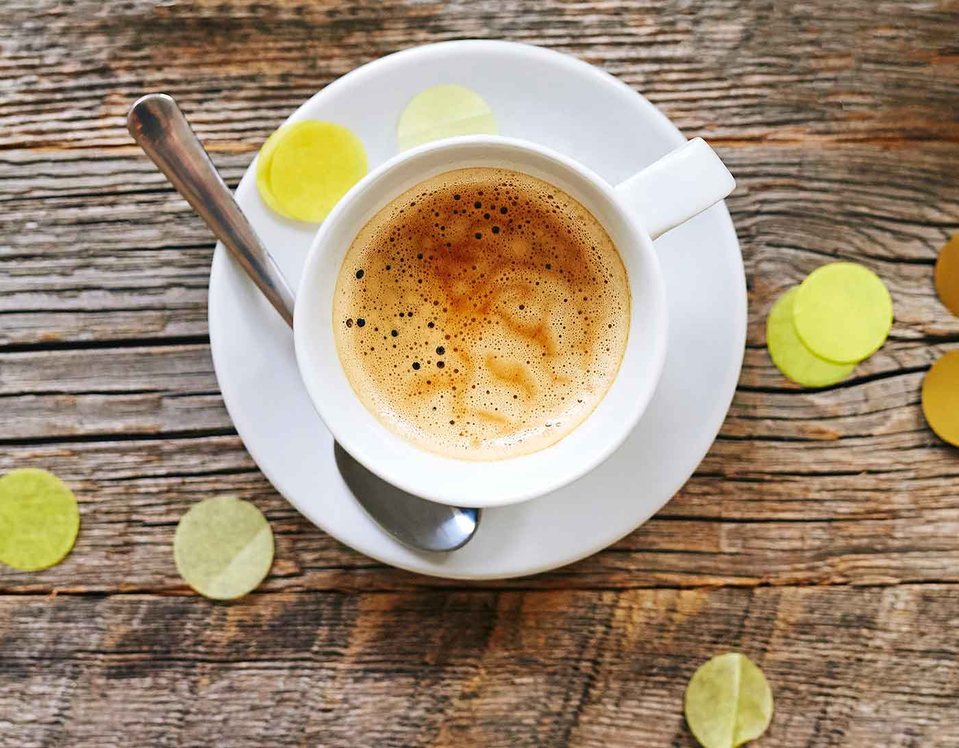 En kaffekopp på fat på ett grovt träbord i grånat trä