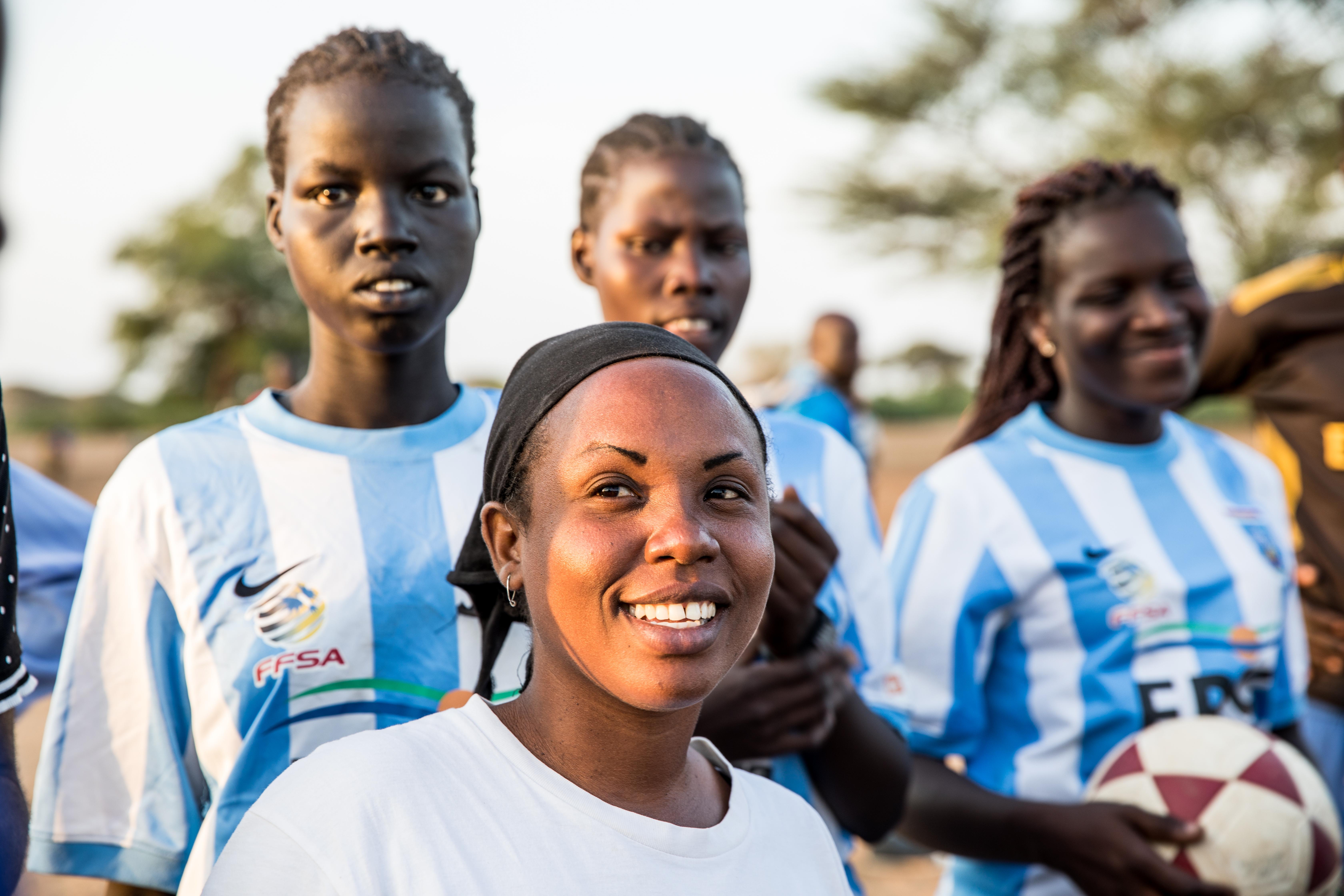 En leende kvinna i förgrunden, bakom tre personer i fotbollströjor varav en håller i en fotboll