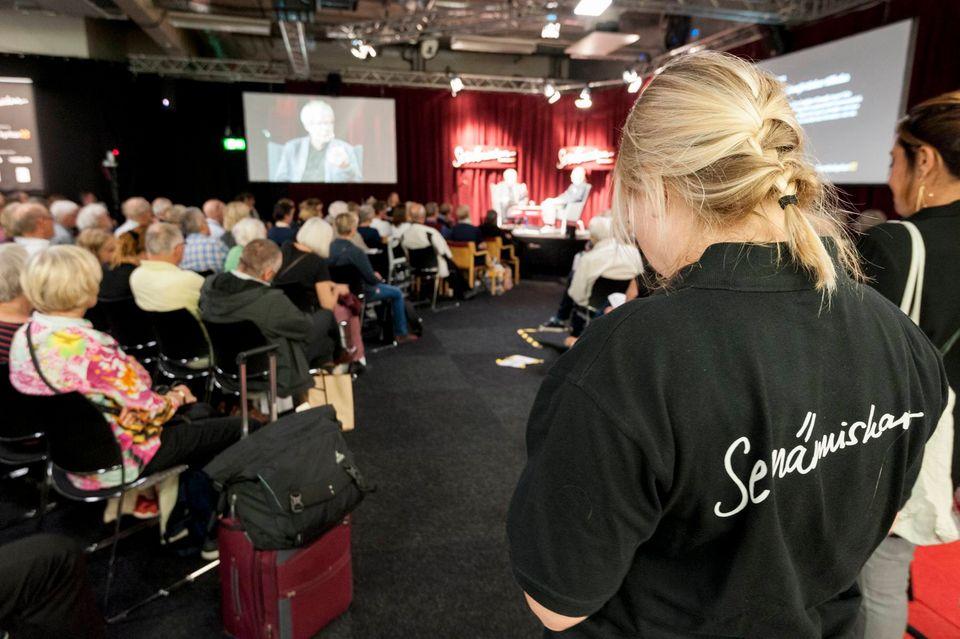 """I förgrunden står en person där texten """"Se människan"""" syns på ryggen. I bakgrunden en publik som lyssnar på samtalet som pågår på scenen."""