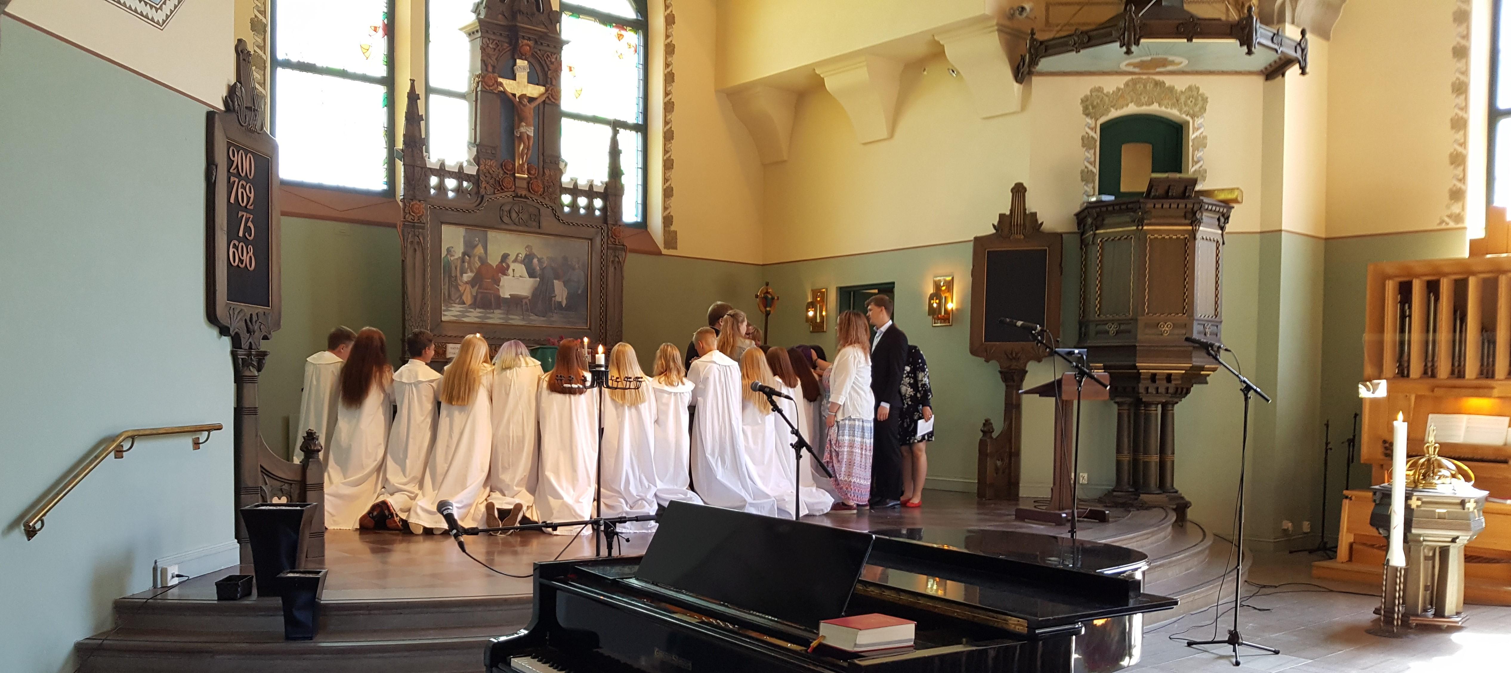 Handpåläggning på en av konfirmanderna som knäböjer runt altaret.