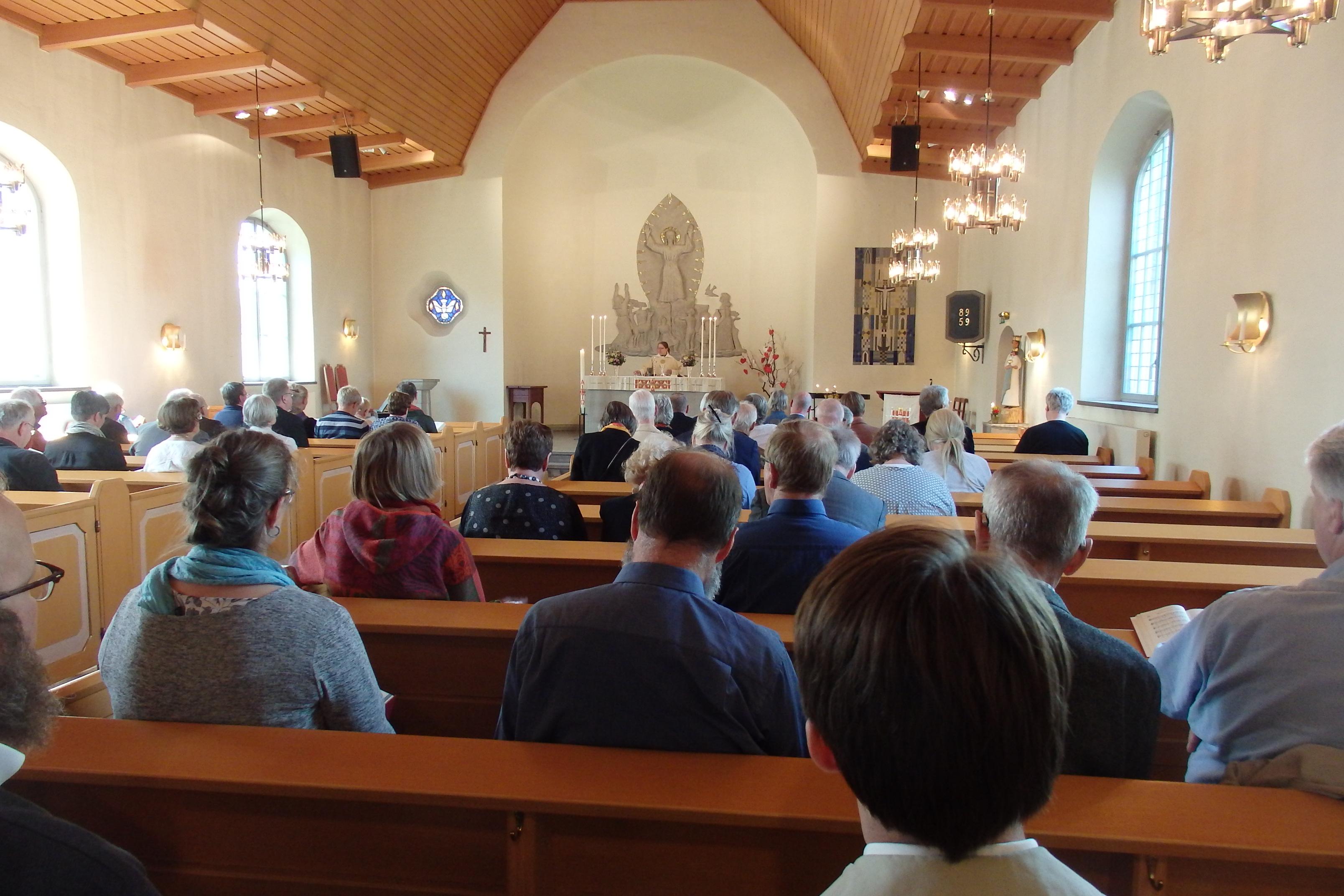 En fylld kyrka med prästen fram vid altaret