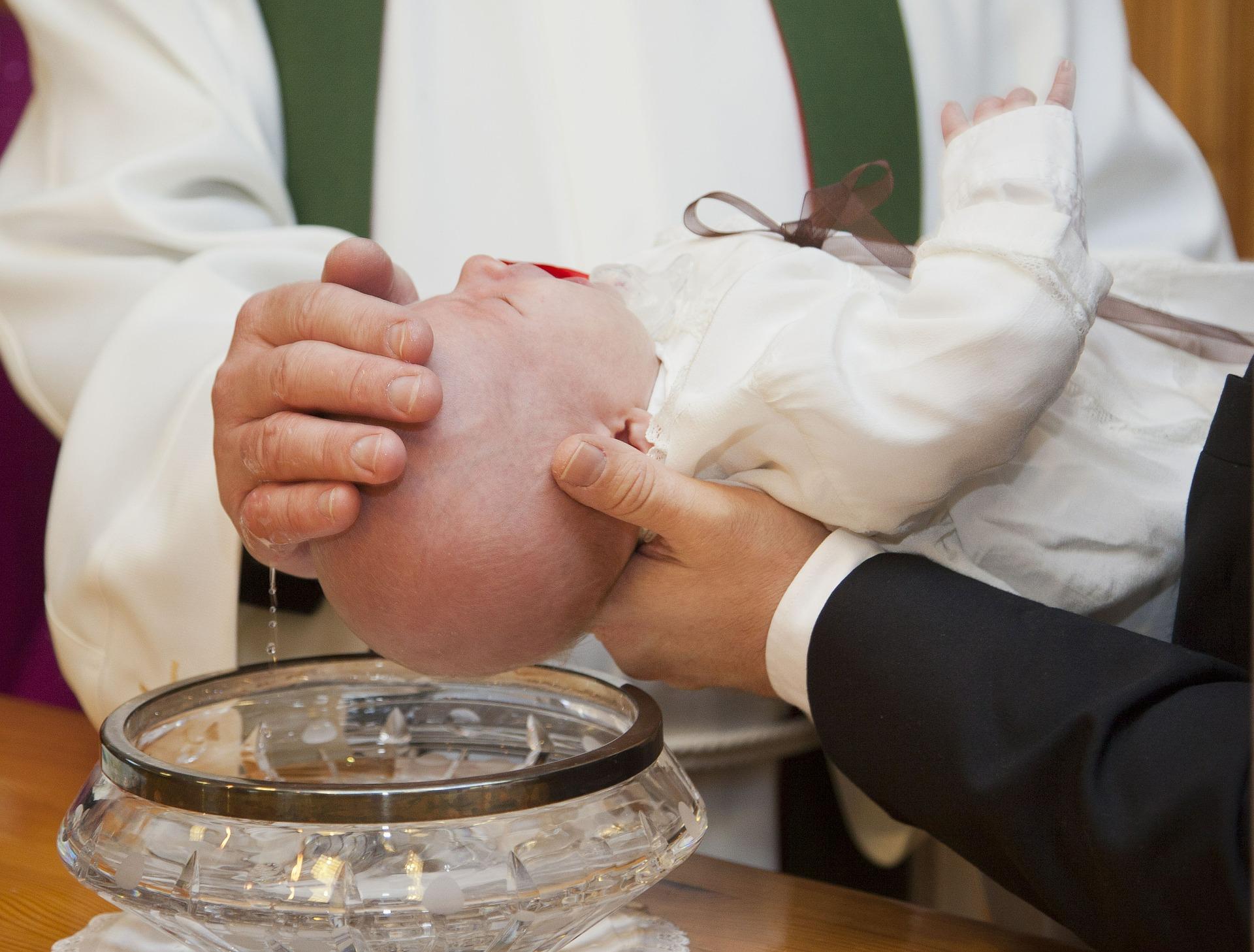 En bäbis som döps över en dopfunt av glas