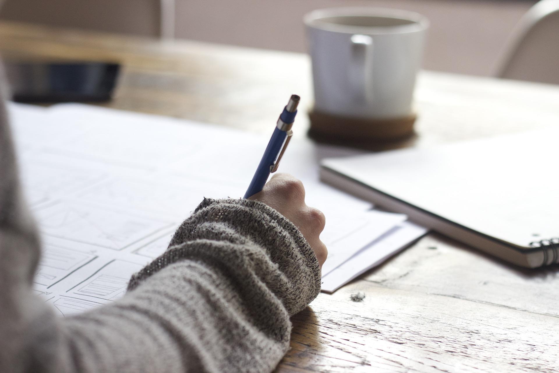 En hand som skriver anteckningar på ett papper