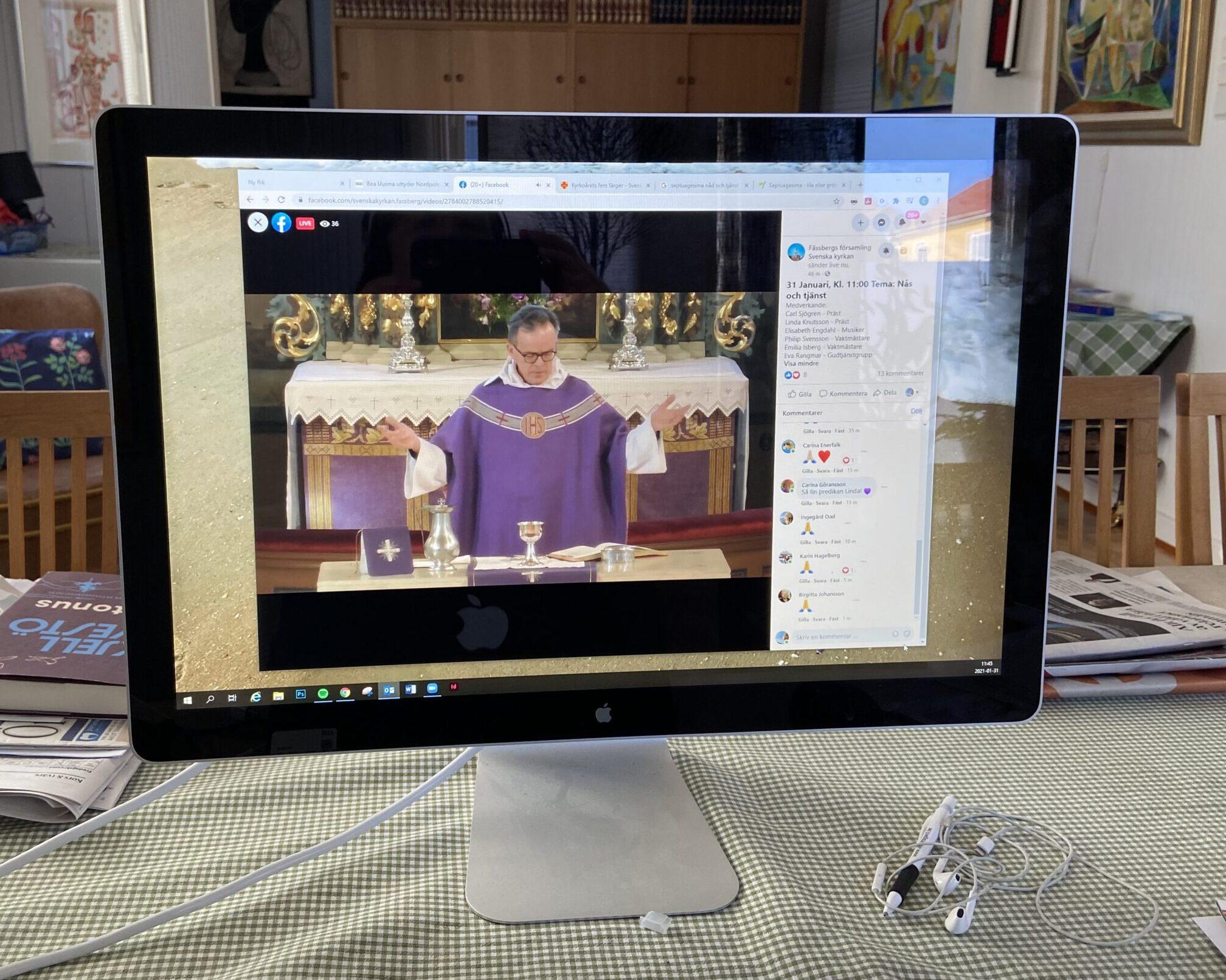 En dator står på ett bord och visar en gudstjänst som sänds digitalt.